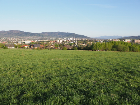 Colored cityscape landscapes of european Bielsko-Biala city and countryside of grassy field at Beskid Mountains in POLAND with green plants, clear blue sky in 2018 warm sunny spring day on June