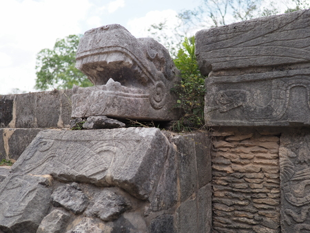 Ancient sculpted stony snake head of great ball court building at Chichen Itza city in Mexico with cloudy sky in 2018 warm winter day, North America on February