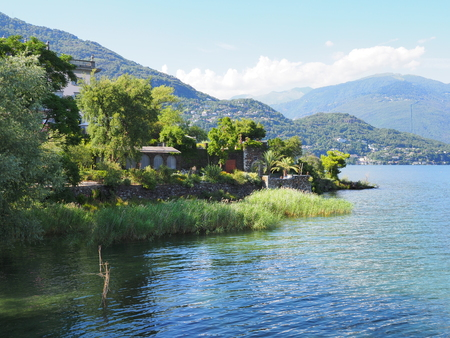 Beautiful shore of swiss Brissago island at alpine Lake Maggiore landscapes near european city of Ascona at canton Ticino in Switzerland with clear blue sky in 2017 warm sunny summer day on July.