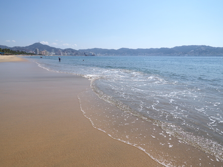 Wonderful panoramic view of sandy beach at bay of ACAPULCO city in Mexico and waves of Pacific Ocean with clear blue sky in 2018 hot sunny winter day, North America on March.