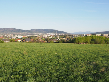 Calm panorama of cityscape european Bielsko-Biala city and countryside landscapes of grassy field at Beskid Mountains in POLAND, green plants, clear blue sky in 2018 warm sunny spring day on April