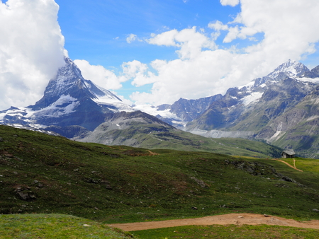 Impressive Matterhorn mount in clouds and alpine mountains range landscapes in swiss Alps seen from Gornergrat in SWITZERLAND with cloudy blue sky in 2017 warm sunny summer day, Europe on July.