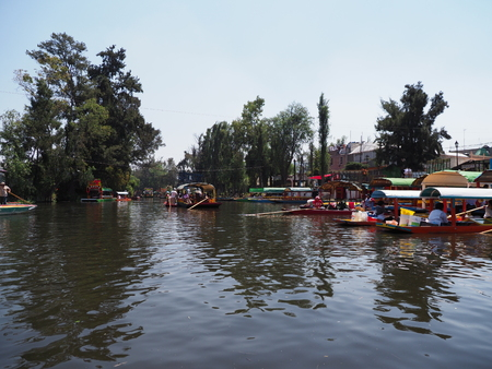 Impressive colorful mexican boats with tourists and gondoliers at Xochimilcos Floating Gardens in Mexico