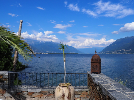Panorama on swiss Lake Maggiore seen from Brissago island near european Ascona city at alpine landscapes at Canton Ticino in Switzerland, cloudy blue sky in 2017 warm sunny summer day on July. Banco de Imagens