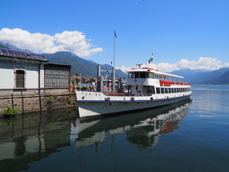 Paddle-wheel steam boat moored ready to cruise at promenade on alpine Lake Maggiore landscape in Locarno at Switzerland