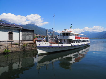 LOCARNO, SWITZERLAND EUROPE on JULY 2017: Paddle-wheel steam boat moored ready to cruise on promenade on alpine Maggiore Lake in european swiss travel scenery, clear blue sky in warm sunny summer day. Editorial