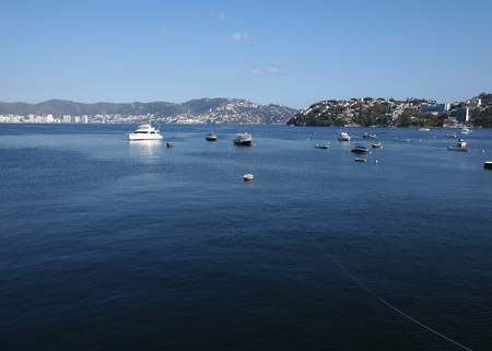 Amazing panorama of fishing and motor boats at bay of Acapulco city in Mexico and mexican landscapes of Pacific Ocean with clear blue sky in 2018 hot sunny winter day, North America on March.