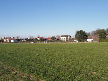 Green grassy field and houses at european Bielsko-Biala city in Silesian district in Poland, clear blue sky in 2020 warm sunny spring day on April.