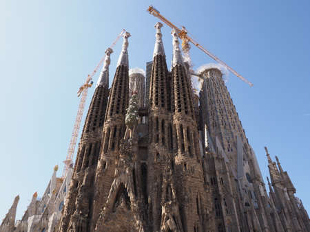 BARCELONA, SPAIN on SEPTEMBER 2019: Front of cathedral Sagrada Familia under construction in european city at Catalonia district, clear blue sky in warm sunny summer day. Editorial