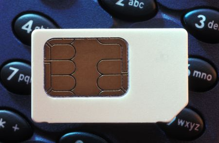 sim: A mobile phone sim card on top of a phone keypad. Stock Photo