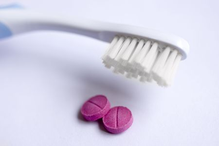 tooth brush and two dental disclosing tablets Stock Photo