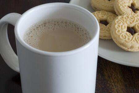 jam biscuits: una tazza di t� bianco e biscotti marmellata piatto Archivio Fotografico