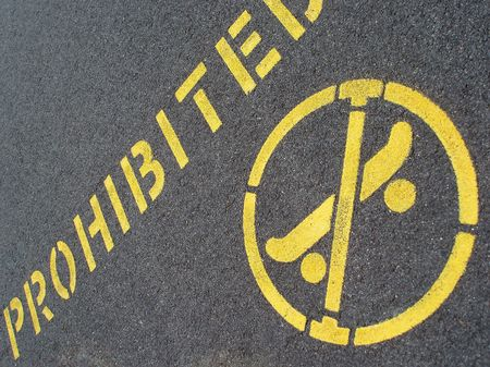 skateboarding prohibited sign on a tarmac pavement photo