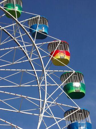 a colourful fairground wheel against a blue sky Stock Photo