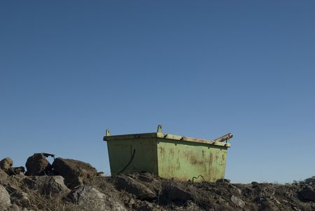 rusty green skip on a building site, surrounded by rubble photo
