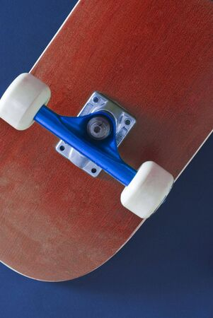 the underside of a red coloured skateboard on a blue background