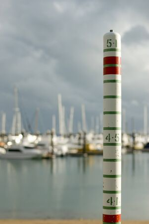 surge: Yachts sheltering in a marina with storm clouds. Concept of a storm surge rising tide