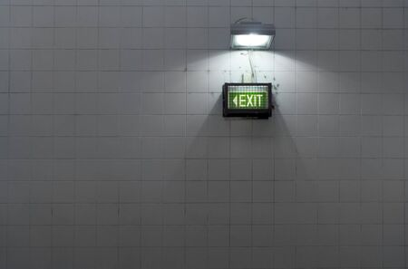 A grungy subway exit sign on a tiled wall Stock Photo