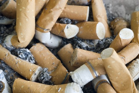 An ashtray full of ash and cigarette butts