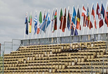 Rows of seats in a temporary stadium with flags of various nations