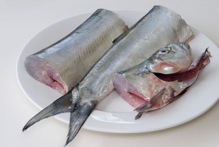 a fresh ribbon fish on a plate, cut into three pieces ready for filleting Stock Photo