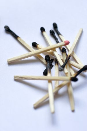 burned out: a pile of burnt matches with one head still unburned