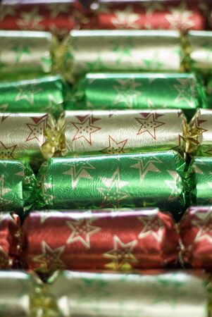 a line of metallic christmas crackers pictured with a narrow depth of field