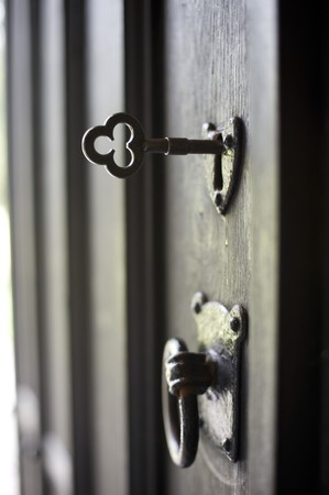 an open antique door with key in the lock photo