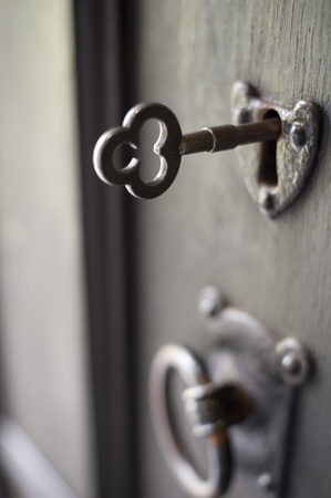 antique key: an old door handle and lock with a key in it, pictured with a narrow depth of focus