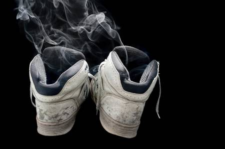 dirty old pair of sneakers on a black background