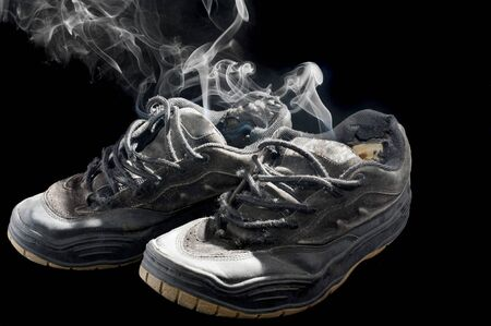 pair of smelly old sneakers on a black background