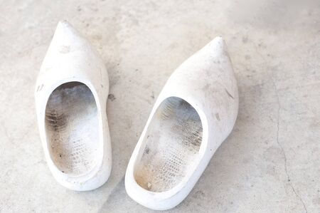 undecorated: pair of undecorated white wooden clogs on a dirty concrete floor Stock Photo
