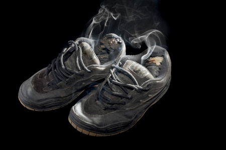 rotten pair of dog-eared old sneakers on a black background