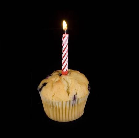 velitas de cumpleaños: magdalena con una vela encendida en la parte superior Foto de archivo