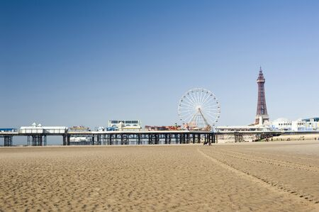 View across the sand of Blackpool Beach to the pier with the historic Blackpool Tower and pier in the background Stock Photo