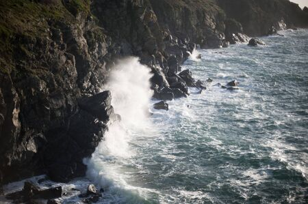 tempest: spray flying off a rock as a breaking wave crashes ashore on a rugded rock coastline