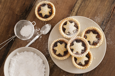 Traditional Christmas fruit mince pies decorated with pastry stars on a kitchen table ready to be sprinkled with powdered icing sugar in a sieve for a delicious seasonal teatime snack, overhead view