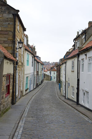 whitby: View along the length of the narrow cobbled Henrietta Street, Whitby, North Yorkshire with its traditional historical English cottages