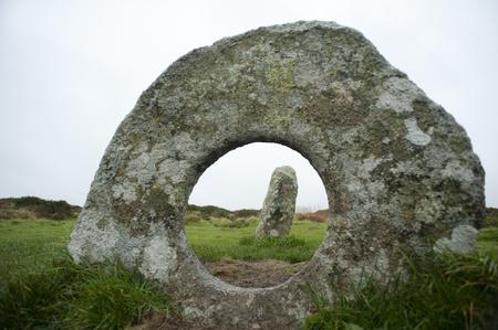 crick: Guarda attraverso il foro circolare al centro della pietra round di Men-an-tol, Cornwall, una disposizione neolitico preistorico di megaliti di granito vicino Morvah