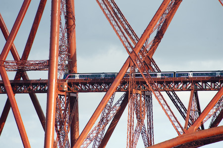close up on train crossing the forth bridge showing the complex structure of metal tubes and girders photo