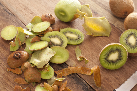 kiwifruit: Preparing a tropical kiwifruit dessert with a high angle view of peels, peeled kiwi fruit and sliced fruit being prepared in a rustic country kitchen Stock Photo