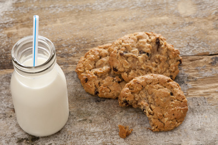 milk and cookies: Small glass bottle of fresh creamy farm milk with a straw alongside half eaten crunchy cookies on a rustic wooden surface, high angle view Stock Photo