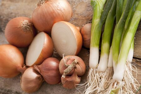 pungent: Fresh whole and halved brown onions with a bunch of young scallions to be used as a pungent flavoring in cooking or salads, close up overhead background view Stock Photo