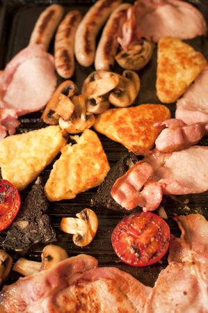papas doradas: Cocinar el desayuno para una familia con una vista a�rea de cerca de bacon, croquetas de patata, salchichas, tomate y champi�ones chisporrotea en una plancha caliente Foto de archivo