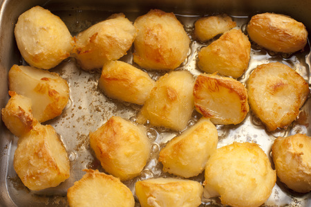 Catering background of delicious golden roast potatoes in a hot roasting pan fresh from the oven