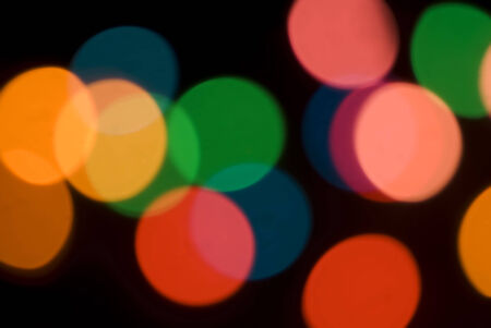 Bokeh of colorful party lights in red, orange and green for a festive background for a celebration or holiday Stock Photo
