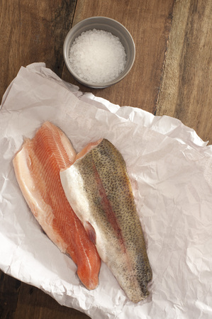 rock salt: Top View of Fresh Rainbow Trout Meat on a Paper Placed on Wooden Table with Rock Salt on a Saucer. Stock Photo