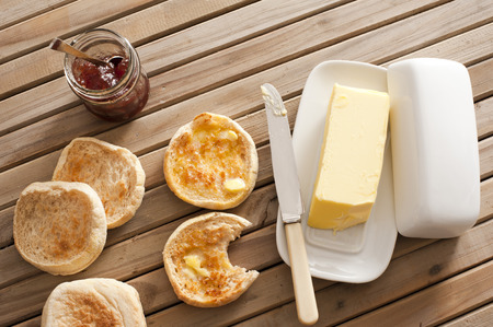 mantequilla: Vista elevada de tostadas molletes ingleses con mantequilla y mermelada en la cima de la tabla de madera Foto de archivo