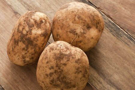 accompaniment: Close up view of three unwashed fresh farm potatoes with clinging soil on a rustic wooden table for a healthy nutritious vegetable accompaniment to a meal