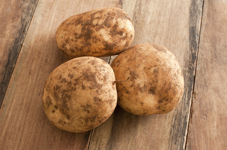 unwashed: Close up Three Unwashed Fresh Potatoes on Top of a Wooden Table.